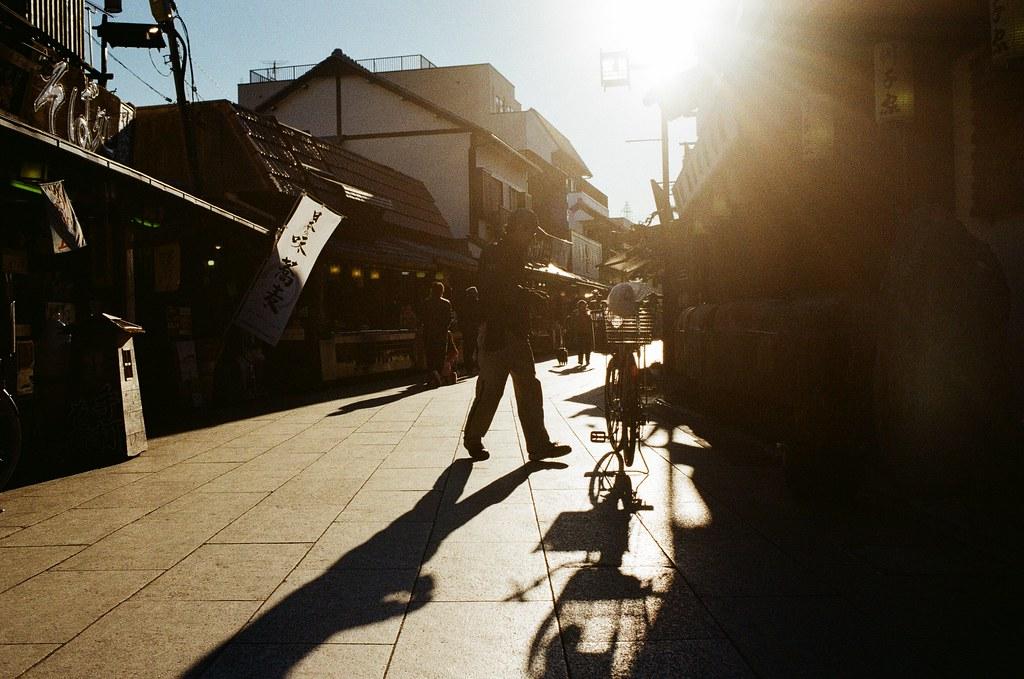 柴又 Tokyo, Japan / Kodak ColorPlus / Nikon FM2 一天下午去了一趟柴又,之前去過新柴又,然後走到河堤去看花火,那是那年夏日的時候。  回來之後發現原來柴又有很多特色,決定這趟一定要過去走走。  柴又老街剛好是東西向,黃昏的時候可以拍逆光,不過周圍的店家也在這個時候開始打烊,還好我有稍微早一點出門。  這條街來回走了兩趟,也找一間店家吃飯,還有神奇的麻糬!  黃昏街道陽光很刺眼,隱約看到前方有人騎腳踏車在發送傳單,我就蹲在路邊,嘗試對焦在腳踏車上拍下!  Nikon FM2 Nikon AI AF Nikkor 35mm F/2D Kodak ColorPlus ISO200 0397-0039 2017-01-26 Photo by Toomore
