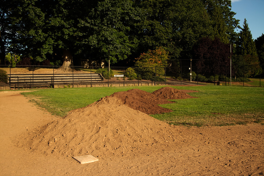 Four mounds of dirt await being spread onto a baseball diamond