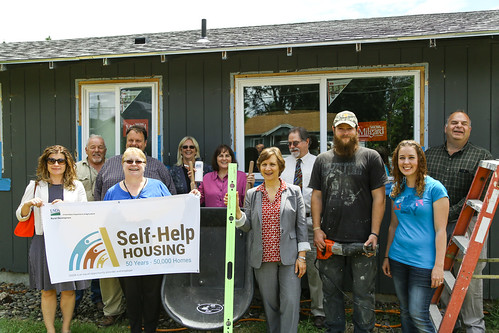 USDA Rural Development State Director Vicki Walker (center with wheelbarrow), U.S. Representative Suzanne Bonamici (center with level), local nonprofit Community Action Team (CAT), and community leaders with first-time homeowners Jessica and Jason Smith