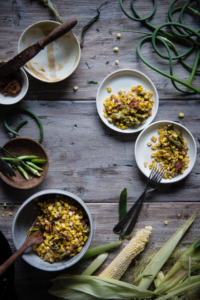 charred corn with miso butter, bacon, & garlic scapes | two red bowls