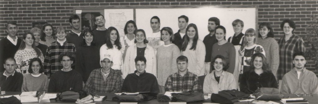 greyscale photo of a group of students with two faculty members, all dressed in winter clothing