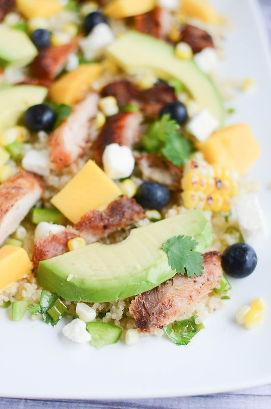 Blackened Chicken and Quinoa Salad - quinoa topped with blackened chicken, avocado, mango, bell peppers, corn, blueberries, feta, and a lime vinaigrette!