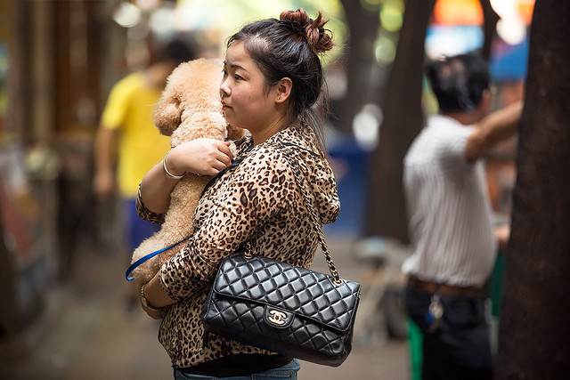 Woman with Chanel bag and dog in Beijing, China.