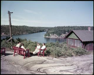 Two men and two women seated outside a cabin on the water, ca. 1950 / Deux hommes et deux femmes assis à l'extérieur d'un chalet au bord de l'eau, vers 1950