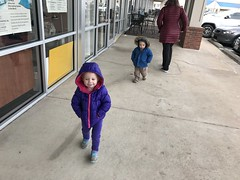 The twins both walking with their hands in their pockets in the cold