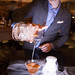 Pouring the A Curtsy and A Bow cocktail with tonka fog spilling out from the carafe