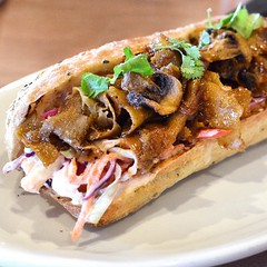 "Korean BBQ Sub, on the new summer menu at @nativefoodscafe. I'm not sure how this qualified as ""Street style Korean"" seitan but with the pineapple slaw (also not Korean) and crispy mushrooms on a multi seed baguette it was a tasty--but messy--dish. I woul"