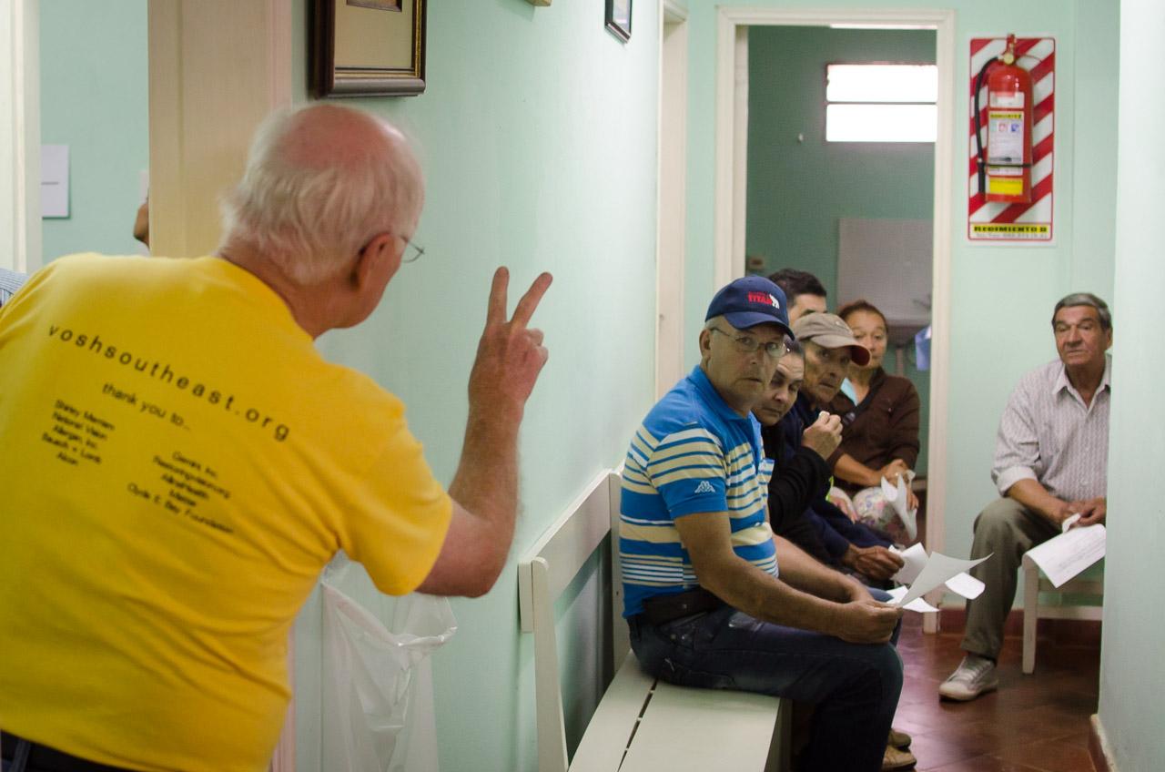 El líder y director administrativo Charles Covington llama a dos pacientes más para realizarles pruebas con los instrumentos de precisión. Los voluntarios de V.O.S.H, en su mayoría norteamericanos, aprendieron a comunicarse con los pacientes en español y en guaraní, a medida que transcurrían los días en la misión. (Elton Núñez)