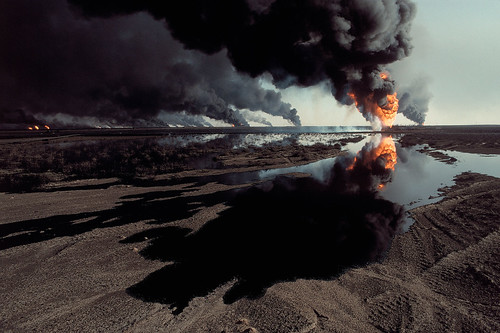unrar: Kuwait, 1991. Burgan oil fields. A lake of spilled oil. Burning oil tanks in the background, Bruno Barbey.