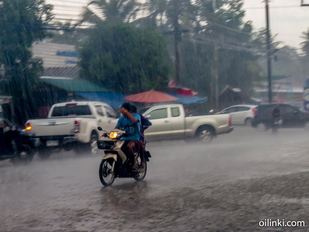 No worries, although it's a bit hard to see forward. Driving motorbike in the rain. Phuket, Thailand
