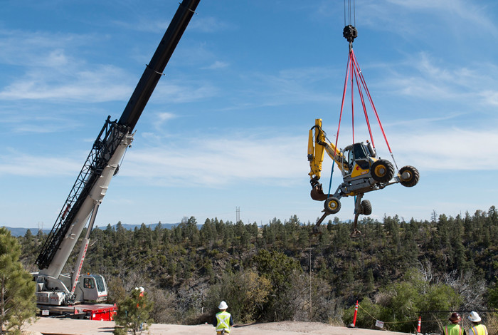 A telescoping crane hoists a spider excavator over Los Alamos Canyon before placing it on the canyon slope to excavate historically contaminated soil.