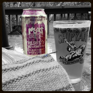 Rainy day deck #knitting is better with a #moatmountainbrewingco #missvsblueberrybeer even if it's in a #pumpkinhead pint glass with not freshly picked #blueberries #blueberrybeer #craftbeer #madeinnh #603 #drinklocal #drinkstagram #knitstagram #moatmount