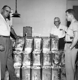 Law enforcement officers with moonshine seized during a raid, Tallahassee
