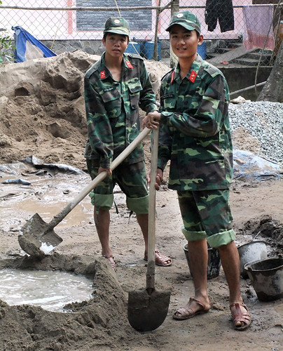 Vietnamese soldiers building low-cost houses for people living along the Mekong River