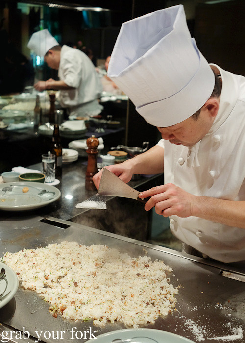 Tapping salt over the fried rice at Wakkoqu, Kobe, Japan