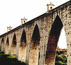Aqueduto das Águas Livres, Lisbon, Portugal  O Aqueduto das Águas Livres ergue-se sobre o vale de Alcântara, na cidade de Lisboa, em Portugal.  Considerado como um dos locais mais bonitos de Lisboa na actualidade, a construção de um aqueduto para levar água à cidade deu, a D. João V (1706-1750), a oportunidade para satisfazer a sua paixão pelas construções grandiosas, uma vez que a única área de Lisboa que tinha água era o bairro da Alfama.  O projecto foi custeado com a receita de uma taxa sobre a carne, o vinho, o azeite e outros produtos alimentares. Apesar de só ter sido concluído no século XIX, em 1748 já atendia a função de fornecer água à cidade.  Na primeira fase da sua construção, até à chegada a Lisboa em 1748, contou com a participação de arquitectos e engenheiros militares famosos, nomeadamente António Canevari (italiano), Manoel de Azevedo Fortes, Silva Pais, Manuel da Maia, Custódio Vieira (autor da arcaria sobre o vale de Alcântara) e Carlos Mardel (húngaro). Manuel da Maia e Carlos Mardel haveriam de ter, após o grande terramoto de 1755, um papel crucial na reconstrução da Baixa Pombalina. O caminho público por cima do aqueduto, esteve fechado desde 1853, em parte devido aos crimes praticados por Diogo Alves (o Pancadas), um criminoso que lançava as suas vítimas do alto dos arcos depois de as roubar, simulando um suicídio, e que foi o último decapitado da História de Portugal.  Actualmente é possível fazer um passeio guiado pela arcaria do vale de Alcântara. Também é possível, ocasionalmente, visitar o reservatório da Mãe d'Água das Amoreiras.  A sua conduta principal apresenta a extensão de 19 quilómetros, embora o comprimento total, incluindo os canais secundários, seja de 58 quilômetros. Com 127 arcos, a sua parte mais conhecida são os 35 arcos sobre o vale de Alcântara, o mais alto dos quais (o Arco Grande) mede 65 metros de altura e dista 29 metros entre pegões.  Na extremidade do aqueduto, a Mãe d'Água das Amoreiras é uma espécie de castelo que