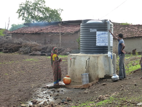 People collect water from a safe water tank at Kalapani