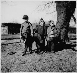 Ann MacDonald, two children and a dog standing next to a tree / Ann MacDonald et deux autres enfants debout près d'un arbre avec un chien
