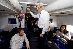 U.S. Secretary of State John Kerry toasts his staff aboard his U.S. Air Force plane on January 18, 2017, as it approached Joint Base Andrews in Camp Springs, Maryland, during the last flight of his tenure as a Cabinet officer after he attended the World Economic Forum in Davos, Switzerland. [State Department photo/ Public Domain]
