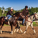 A Pair of Horses and Riders at the Back Stretch by Samantha Decker