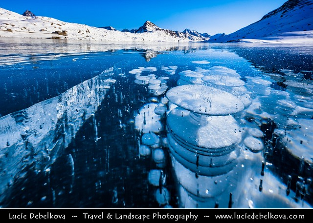 Switzerland - Alps - Deep frozen Lago Bianco - White Lake with surreal bubbles and long ice crack