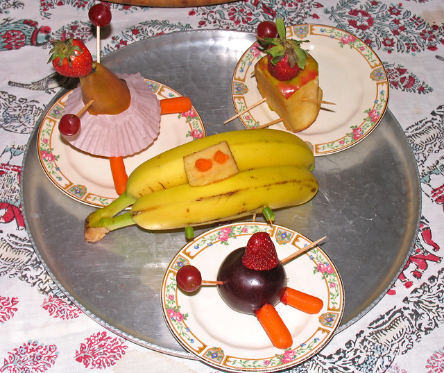 Three Fruit People sitting at a Banana Table