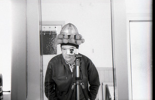 reflected self-portrait with Pentax Espio Mini camera and compound hat