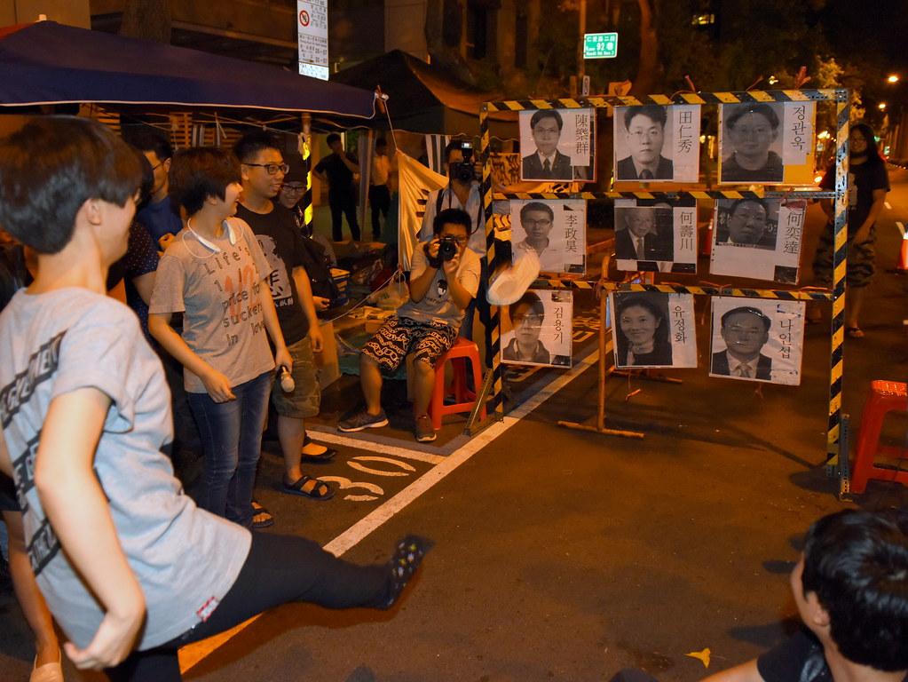 台灣聲援者也將永豐餘集團與韓國Hydis資方代表頭像做成「關廠九宮格」遊戲,讓與會者拿鞋丟擲藉此渲洩資方惡意解僱的不滿。(攝影:宋小海)