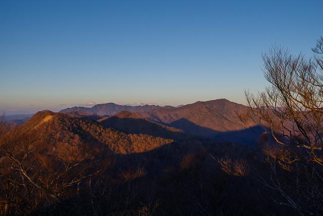 朝陽に染まる山々・・・越えていく石尾根の山々の先に目指す雲取山@鷹ノ巣山