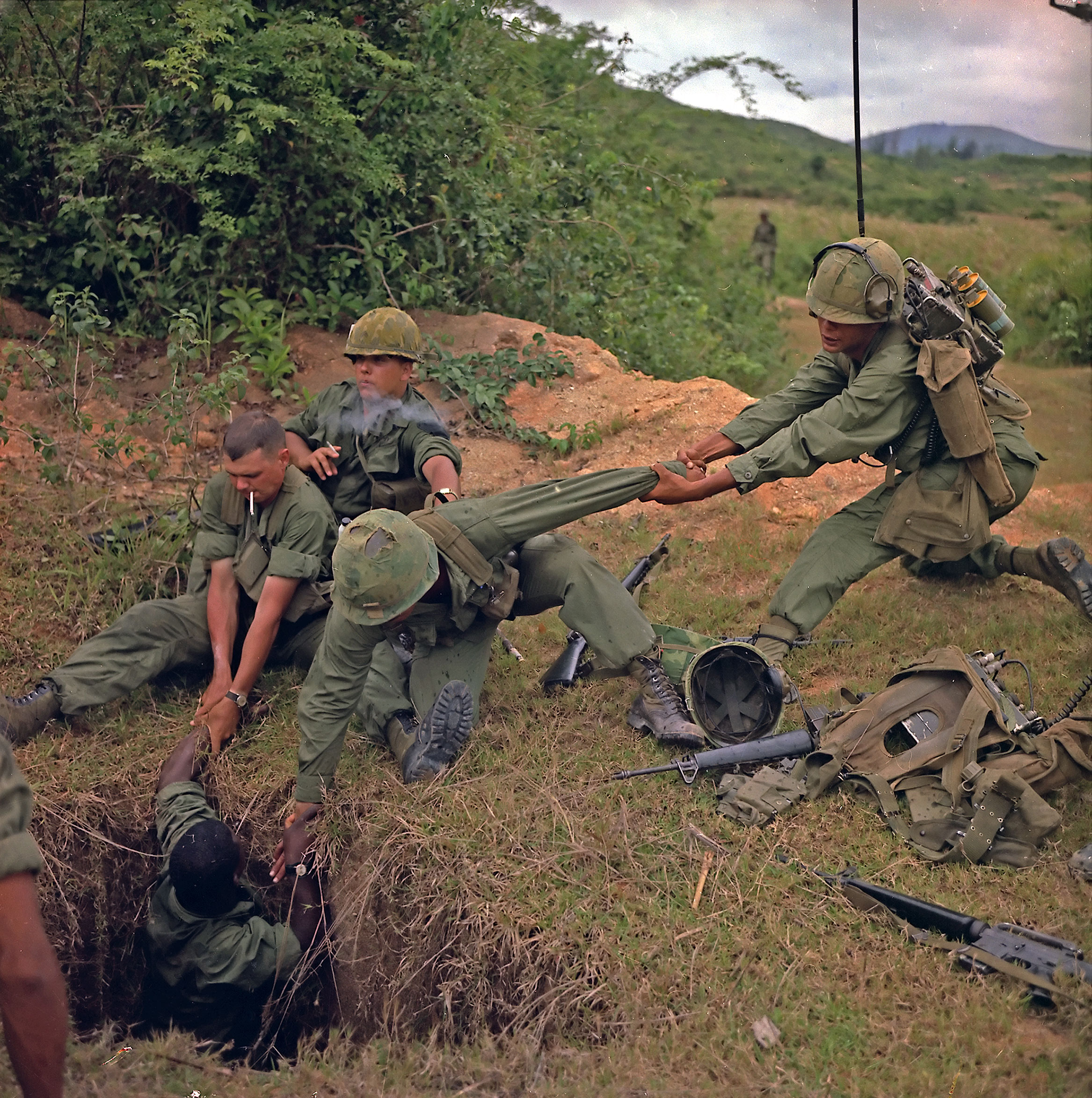 American soldiers pull out a tunnel rat from a North Vietnamese tunnel