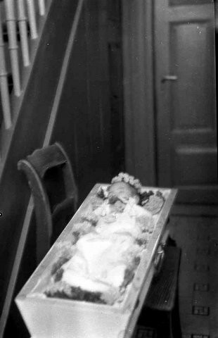 Little girl in open casket at home