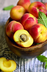 Ripe red apricots in a wooden bowl.