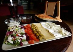 A large white rectangular plate with items arranged in rows running towards and away from the diner: mixed leaf salad with yoghurt dressing, sliced tomatoes, pitted green olives, sliced hard yellow cheese, sliced crumbly white cheese, sliced onions with yoghurt dressing.  In the background is a glass of black tea, a small bowl of yoghurt, a small bowl of honey, and a black square plate with a leaf-shaped flatbread.