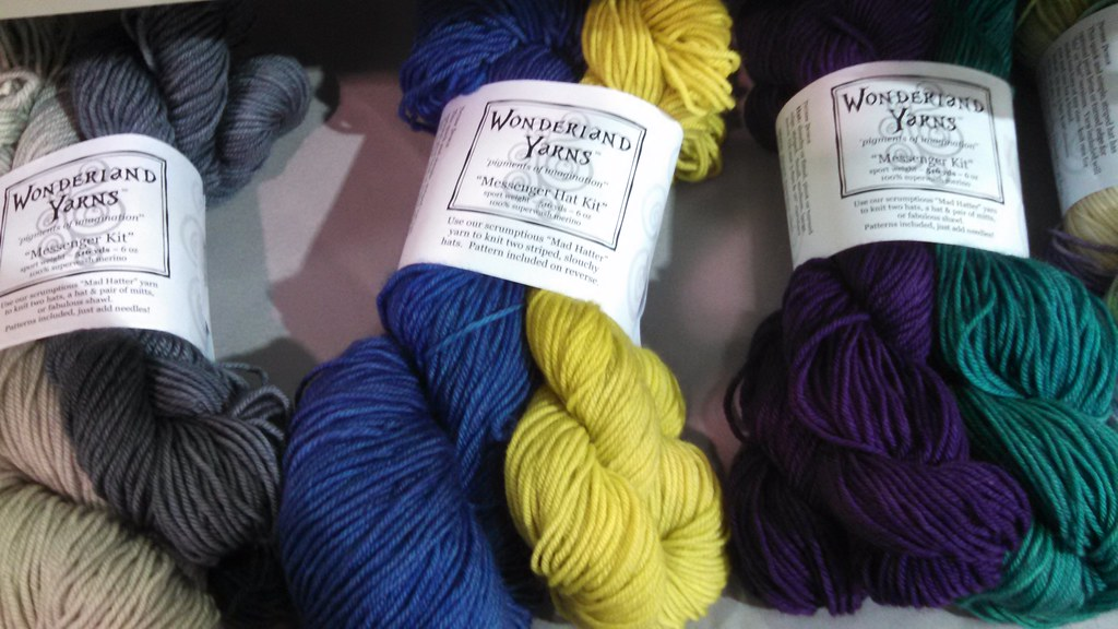 mini-skeins of yarn paired with normal skeins in yellow, blue, grey, and other colors