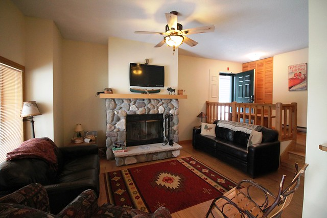 Living area with stone wood burning fireplace and wood floors;
