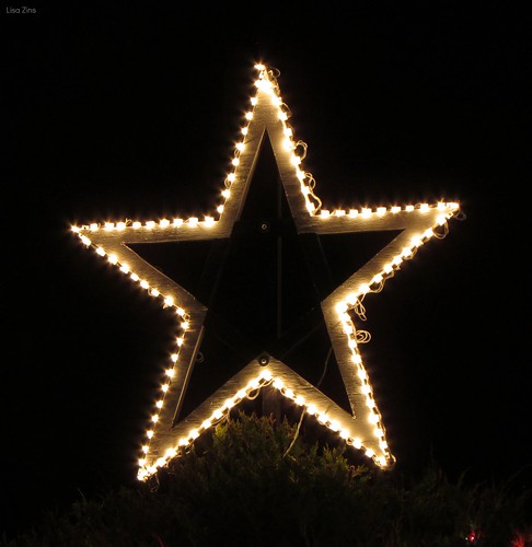 A gold star outline made from lights on a black background