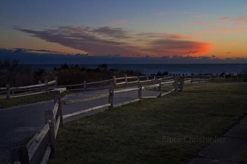 sunrise morning dawn predawn water coast coastal cloud cloudscape orange red blue light fence sun field splitrail rail railing path road