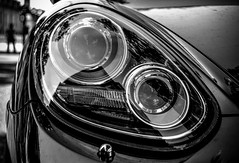 wheel(0.0), rim(0.0), mini(0.0), automobile(1.0), automotive exterior(1.0), vehicle(1.0), automotive lighting(1.0), automotive design(1.0), light(1.0), monochrome photography(1.0), headlamp(1.0), land vehicle(1.0), monochrome(1.0), luxury vehicle(1.0), black-and-white(1.0), black(1.0),