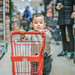 Baby boy pushing shopping cart in supermarket
