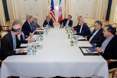 U.S. Secretary of State John Kerry - flanked by National Security Council Senior Director for Iran, Iraq, Syria and the Gulf States Robert Malley, U.S. Energy Secretary Dr. Ernest Moniz, Under Secretary of State for Political Affairs Wendy Sherman, and European Union Deputy Secretary General Helga Schmid - sits across from Iranian Foreign Minister Javad Zarif, Dr. Ali Akbar Salehi, the Vice President of Iran for Atomic Energy and President of the Atomic Energy Organization of Iran, and other advisers on July 1, 2015, in Vienna, Austria, before amid negotiations about the future of Iran's nuclear program. [State Department photo/ Public Domain]