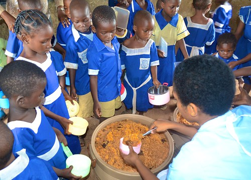 Pupils of St Francis' Catholic Primary School, Ijebu-Itele, being served lunch by students of Louisville Girls High School Bridge of Care Programme