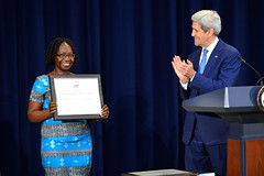 U.S. Secretary of State John Kerry honors Ms. Catherine Groenendijk-Nabukwasi from South Sudan as a 2015 Trafficking in Persons Report Hero at the U.S. Department of State in Washington, D.C., on July 27, 2015. Ms. Groenendijk-Nabukwasi is recognized for her hard work in caring for and protecting children who are vulnerable to trafficking, her steadfast commitment to the right of every girl and boy to an education, and her persistent engagement to increase justice for survivors of modern slavery. [State Department photo/ Public Domain]