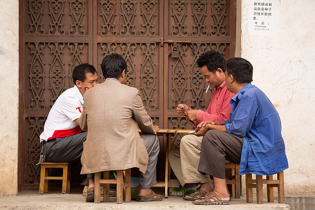 Men playing cards in the streets of Yuanyang Old Town, China.