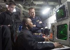 Ensign Robert Prine, left; Capt. Brian Finman, Expeditionary Strike Group 7's deputy chief of staff, right; and Chief Operations Specialist Kevin O. Griffith watch for incoming threats on a radar repeater during a fast attack craft/fast in-shore attack craft exercise aboard USS Bonhomme Richard (LHD 6). (U.S. Navy/MC3 Taylor A. Elberg)