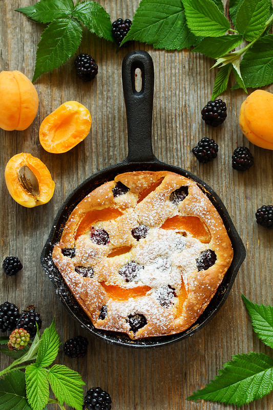 Summer cake Clafoutis with blackberries and apricots. .
