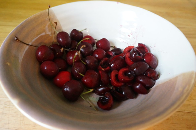 A bowlful of cherries, half whole abs half pitted