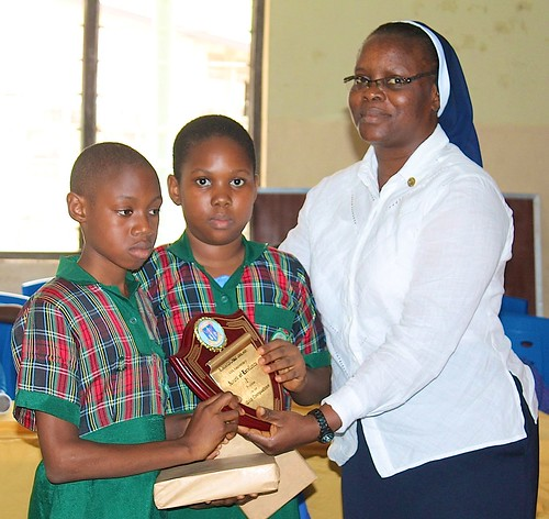 Perpetua Aghoghovia SSL presenting two of the St Louis Nursery and Primary School Students with awards after the special quiz to celebrate the 40th anniversary at the school