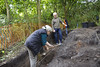 Day4; Anne wields her mattock in trench 3 whilst John keeps an eye out for finds