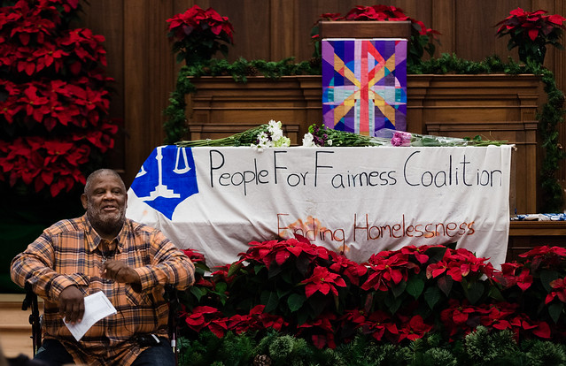 Photo of Steve Thomas sitting leaning on a walker in front of a symbolic coffin.