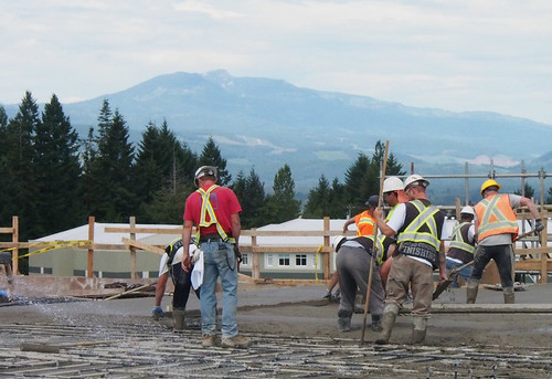 A crew spreads concrete on Level 5 of the new Comox Valley Hospital, with Mt. Washington and the roof of Queneesh Elementary in the background.